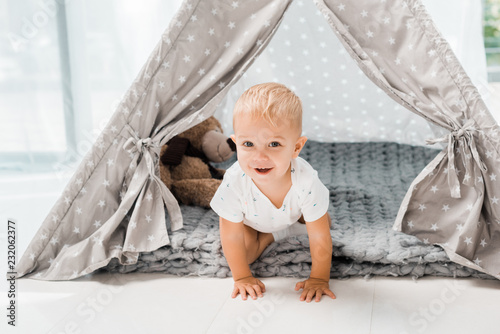 Canvas Print smiling adorable toddler sitting in baby wigwam with fluffy teddy bear toy