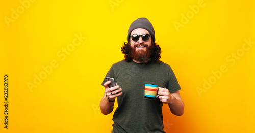 Fotografia Happy bearded hipster man using phone and holding cup of coffee