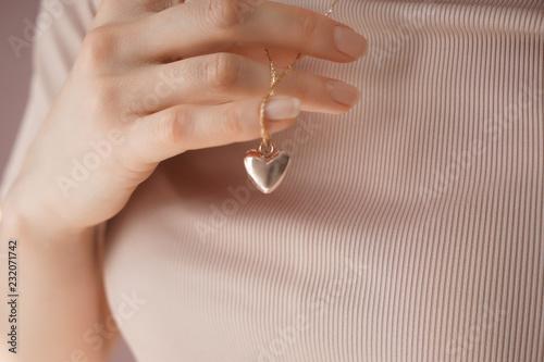 Fotografija Woman wearing heart-shaped pendant, closeup