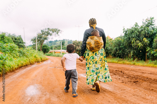 Fényképezés african mother and two children walk alone in red clay road in  village as a fam