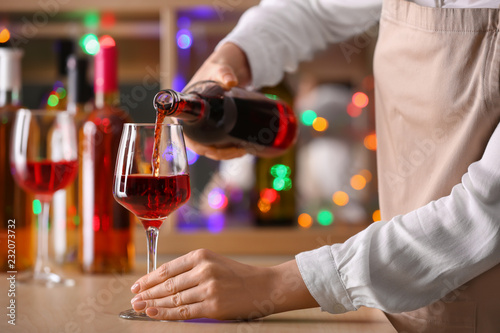 Fotografie, Obraz  Female barman pouring wine from bottle into glass on counter