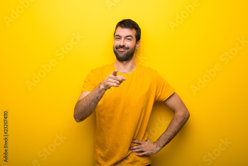 Fotografija  Man on isolated vibrant yellow color points finger at you with a confident expre