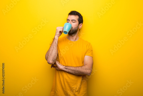 Fotografía  Man on isolated vibrant yellow color taking a coffee in takeaway paper cup and s