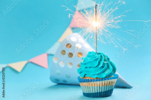 Photo Tasty birthday cupcake with sparkler and party hat on color background