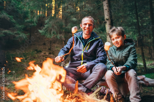 Fényképezés Father and son roast marshmallow candies on campfire in forest