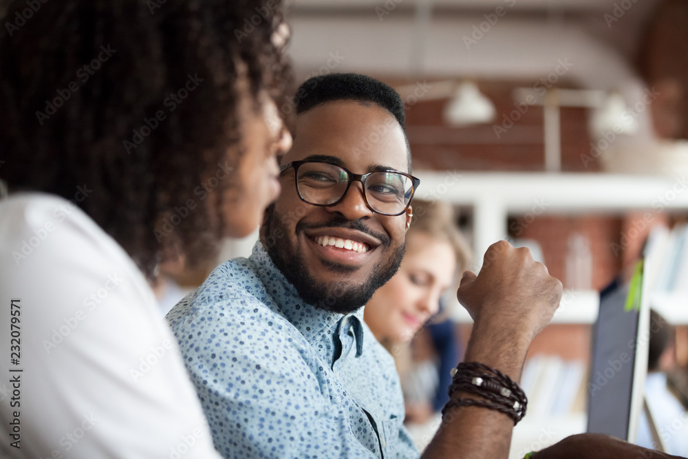Fototapeta Close up of smiling African American employee look at female colleague chatting in office, happy black male worker talk with woman coworker, having casual conversation at workplace, have fun