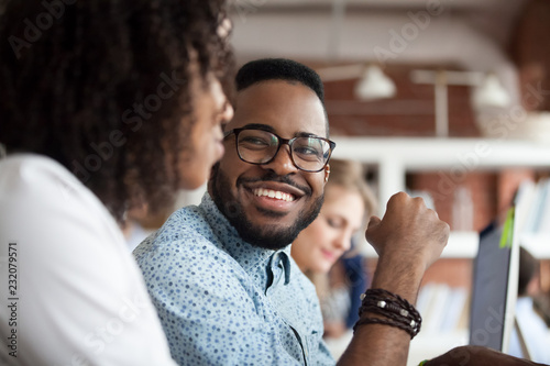 Photo  Close up of smiling African American employee look at female colleague chatting