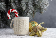 Knitted Winter Cup With Hot Chocolate And Candy Cane On Snowy Table Under Christmas Tree