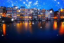 Houses Facades Over Canal With Reflections Illuminated At Night, Amsterdam, Netherlands With Snow