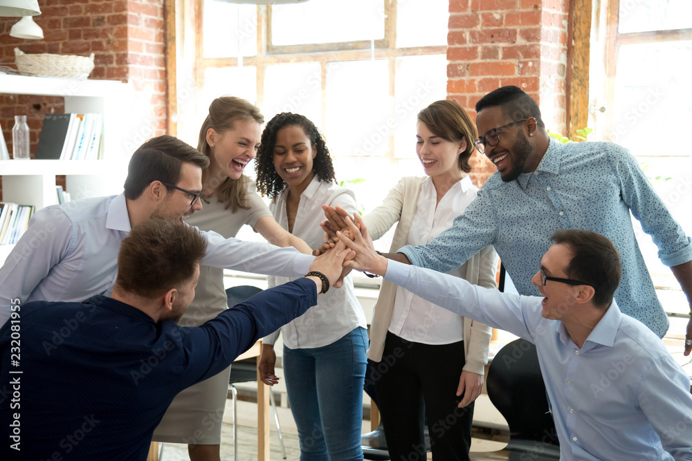 Fototapety, obrazy: Excited multiracial colleagues give high five involved in teambuilding activity at meeting, happy diverse workers join hands celebrate success or win, show team spirit and unity. Cooperation concept