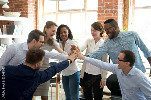 Fotografía  Excited multiracial colleagues give high five involved in teambuilding activity at meeting, happy diverse workers join hands celebrate success or win, show team spirit and unity