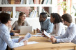 canvas print picture Multiracial millennial colleagues brainstorm discussing startup ideas during briefing in boardroom, female CEO hold business meeting with diverse employees, negotiating analyzing report or stats