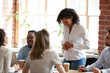 canvas print picture Multiracial colleagues talk during coffee break at business meeting, diverse millennial employees have casual conversation chatting at briefing, workers joke and laugh in coworking loft office