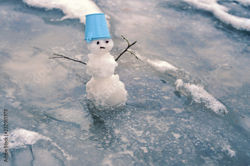 Photo melted snowman in  puddle