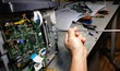 technician repairs photocopier with screwdriver