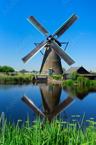 Spoed Foto op Canvas Historisch geb. traditional dutch windmill with reflection at summer day, Netherland