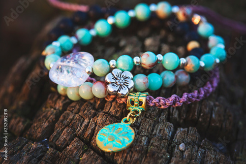 Three bracelets with gemstone beads on wooden background