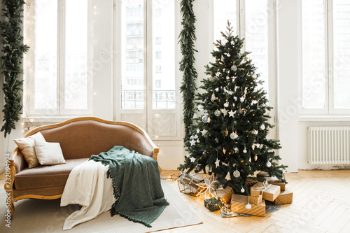 Christmas decor. Bright interior of the living room with large Windows, elegant Christmas tree with toys and garlands and a soft cozy sofa.