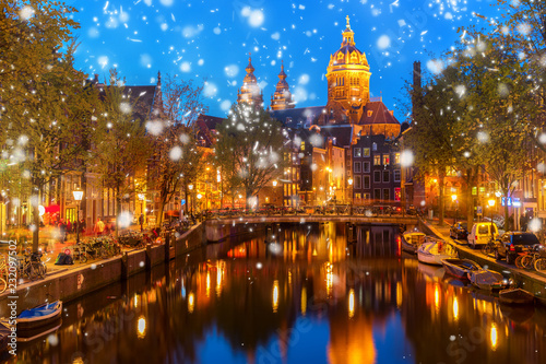 Church of St Nicholas over old town canal illuminated at night with snow, Amsterdam, Holland