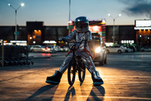 Spaceman In The City At Night On Parking Lot With BMX Bike