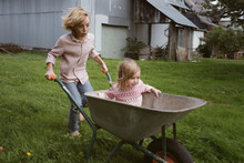 Boy Pushing Wheelbarrow With H...