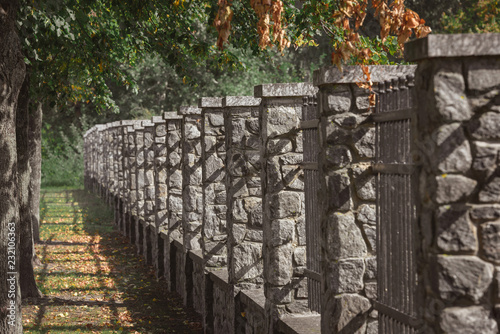 selective focus of stone fence under trees outdoors - Buy