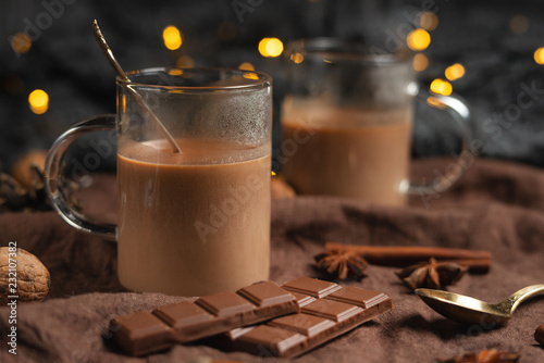 Foto auf Gartenposter Schokolade Christmas or New Year's winter hot chocolate with marshmallow in a dark mug, with chocolate, cinnamon and spices with a festive light garland, selective focus, square culture