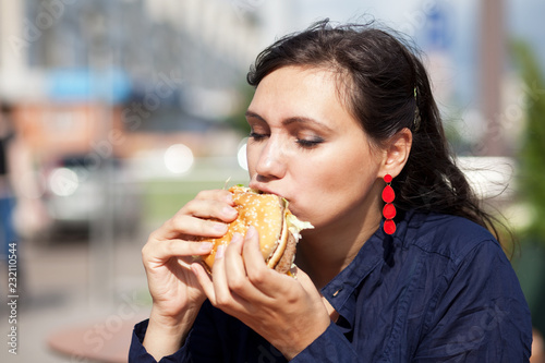 Photo Beautiful girl with an appetite eating a hamburger on the street