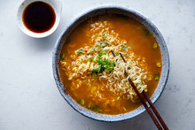 Top View Picture Of Easy Japanese Ramen With Noodles, Pork Broth, Egg And Leek In Handmade Blue Ceramic Bowl With Wooden Chopsticks. Concrete Background