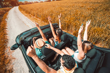 Group Of Happy Friends Having Fun With Hands Up On A Convertible Car At Roadtrip.