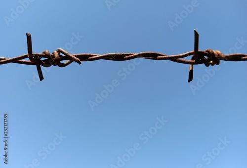 Fotografía  barbed wire on blue sky background
