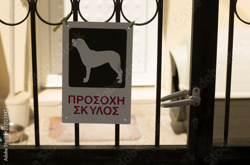 "Fotografía  Warning sign ""Beware of dog"" with the inscription in Greek on the island Crete"