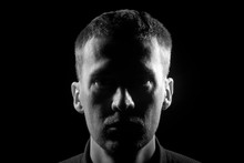 Monochrome Close-up Face Of The Unshaven Man With Bristles Dressed In A Shirt In The Dark, Highlighted On The Left And Right Side And In The Middle Of The Shadow On A Black Isolated Background