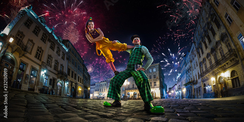 Fototapeta Night street circus performance whit clown, juggler. Festival city background. fireworks and Celebration atmosphere. Wide engle photo obraz