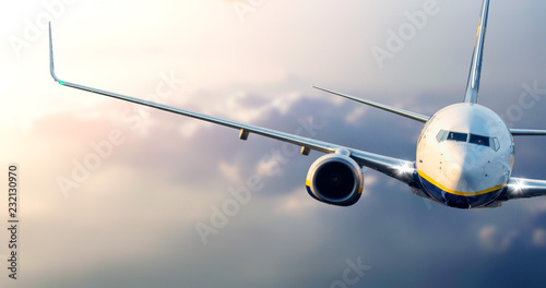 Avion à Moteur Close up of commercial passenger airplane flying above the clouds at sunset