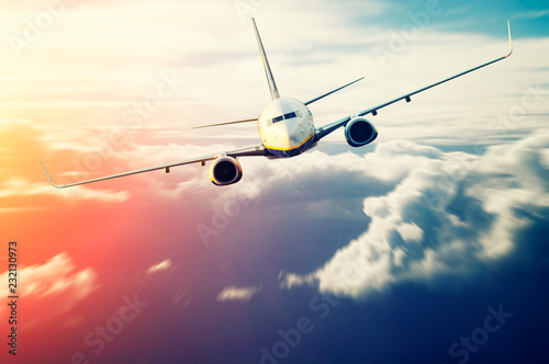 Poster Avion à Moteur Commercial passenger airplane flying above the clouds at sunset, high speed effect on the clouds