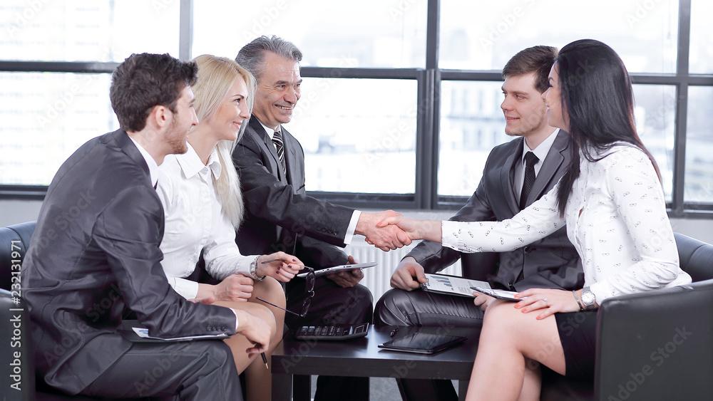 Fototapeta employees look at the handshake of business partners