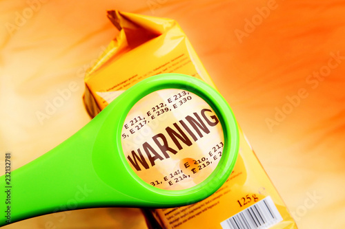 Obraz na plátně Magnifying glass on food additives label with word warning
