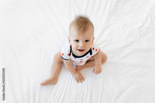 Overhead view of smiling baby sitting on bed