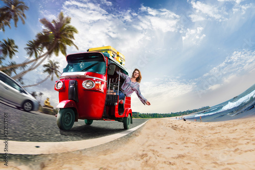Fotografie, Obraz  Happy woman travel by traditional srilankan transport, road near beautiful sea a