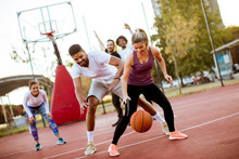 Group Of Multiethnic People  Playing Basketball On Court