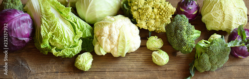 Different varieties of cabbages on wooden background Fototapete