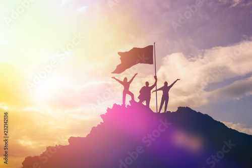 High achiever, silhouettes of three people holding on top of a mountain to raise their hands up Canvas Print