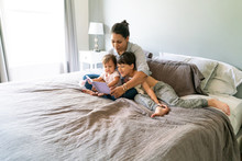Mother And Sons Reading Rook In Bedroom