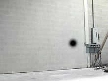 Black Graffiti Spot On A Gray Brick Wall