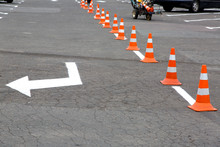Parking For Cars With White Markings And Directional Arrows Fenced With Orange Cones.