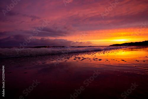 Im Wasser spiegelt sich die über der Ostsee aufgehende Sonne