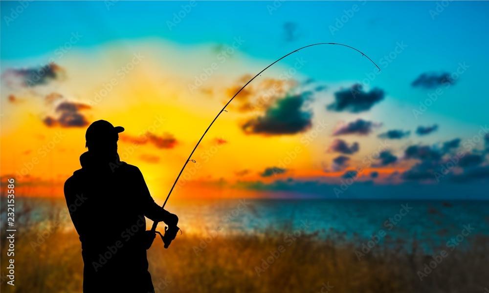 Fototapeta Silhouette of fishing man on coast of sunset sea