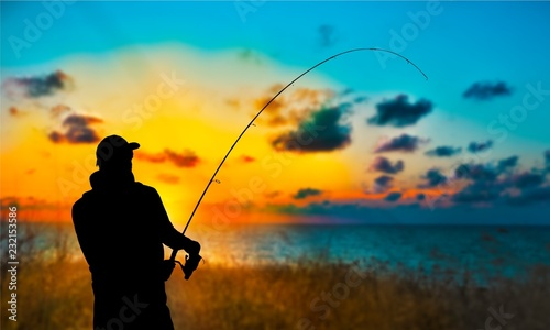 Poster de jardin Peche Silhouette of fishing man on coast of sunset sea