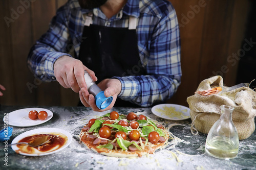 man preparing a pizza, knead the dough and puts ingredients